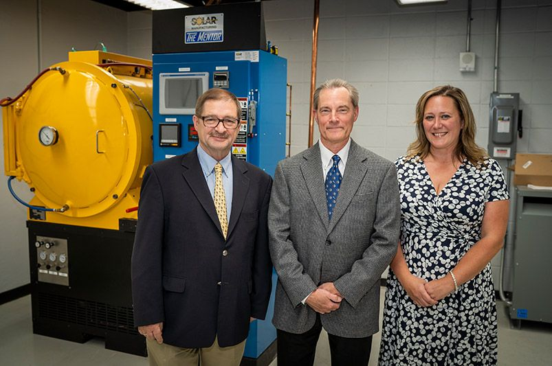 From left, Wojciech Misiolek, Tim Steber, and Laura Moyer with The Mentor, a vacuum heat treating and brazing furnace recently donated by Solar Atmospheres and its CEO and founder, William R. Jones.