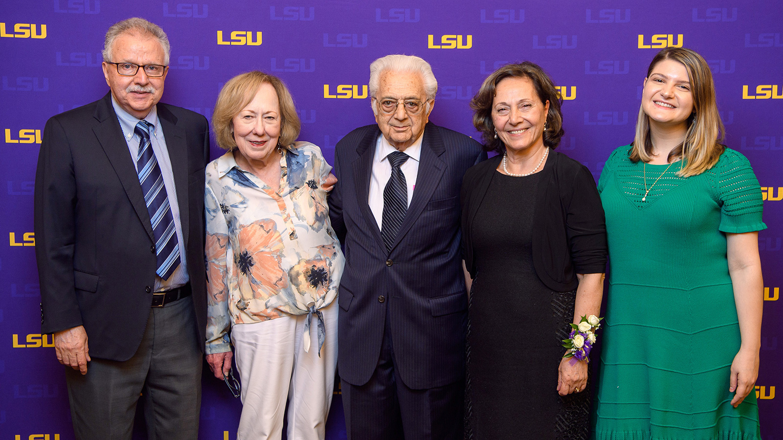 Pamukcu posing with a group of people in front of an LSU step-and-repeat