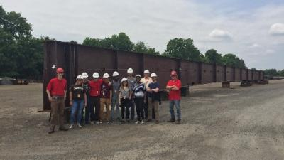 REU students in hard hats pose for a group picture at a site